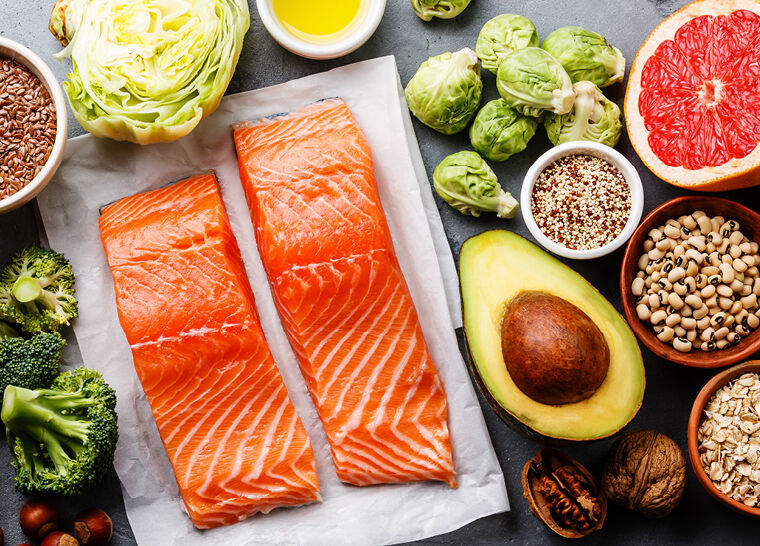 Healthy food for brain health flatlay including salmon, avacados, grapefruit, brussel sprouts and more