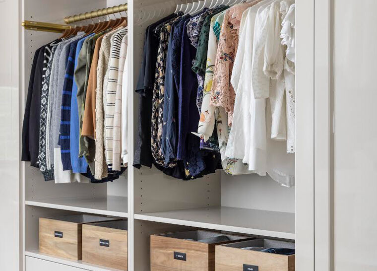 An organized wardrobe with shirts and blouses neatly arranged on hangers