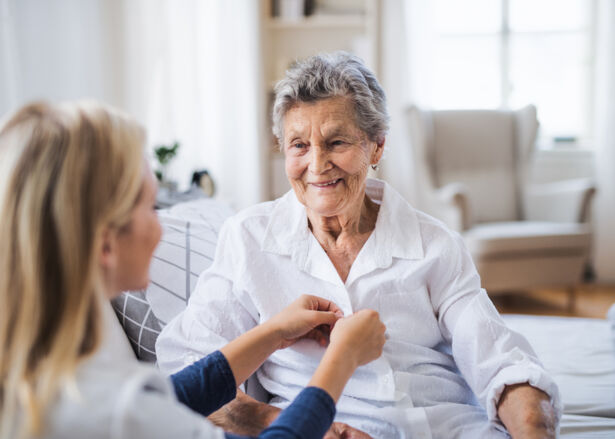 A Team Member helping a happy senior woman sitting on a bed at a residence.