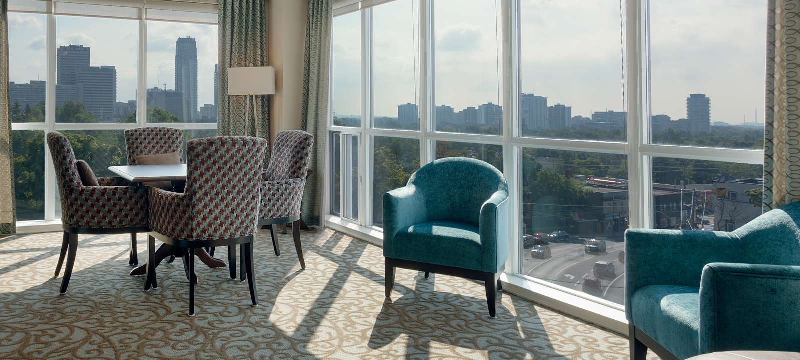 Amica On The Avenue senior living residence sitting area with sunny city view.