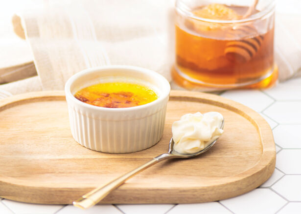 Honey creme brulee on top of a wooden serving tray with a jar of honey in the background