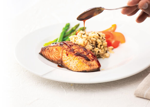 A chef's hand spooning honey ginger glaze over a plate of pan seared salmon
