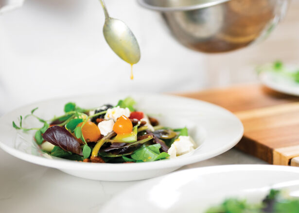 A chef's hand spooning honey vinaigrette dressing over a bowl of salad
