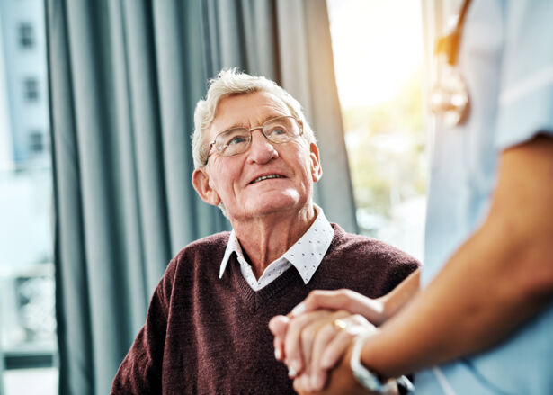 Cropped shot of a male nurse holding hands with a senior patient