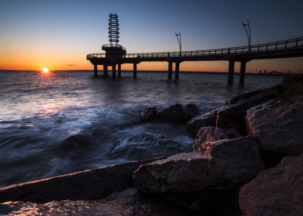 The morning sun reflected on large rocks with lake Ontario and Burlington pier as a backdrop.