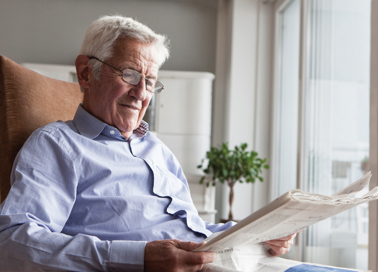 Male senior resident reading newspaper at Amica senior living residence.