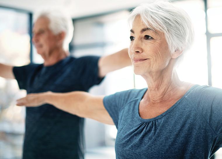 Two seniors exercising in the fitness center at Amica senior living residence.