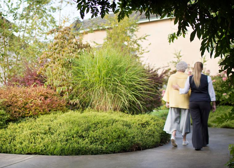 Team member and senior walking along garden at Amica senior living residence.